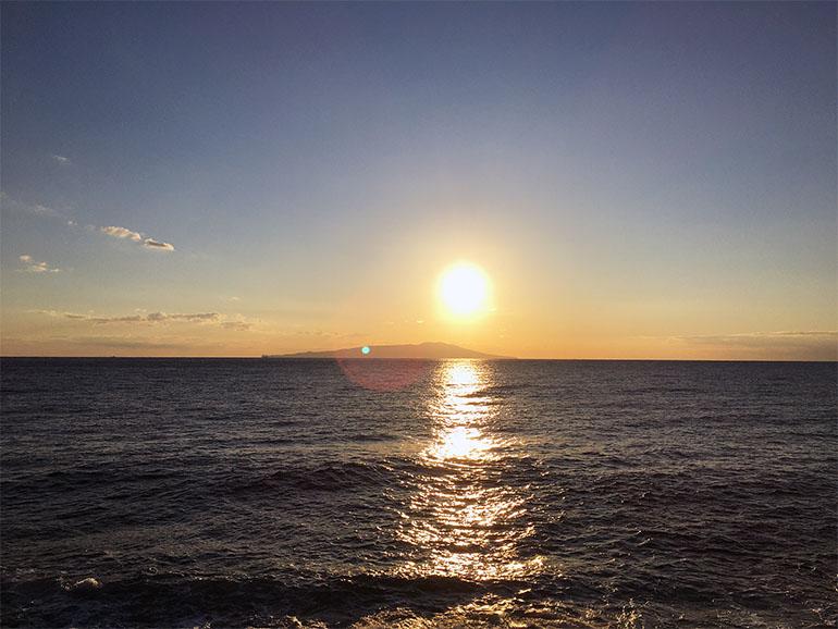 海に夕日が沈んでいく様子