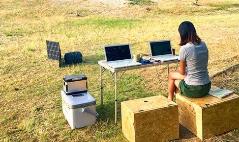 外でパソコンに向かう女性